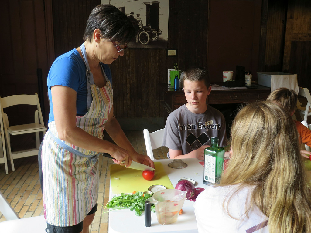 . Liam Nester, 13, of Pittsfield watches as Chef Katherine Miller of Kosmic Kitchen in Lee teaches students in the Food Adventures summer camp at The Mount in Lenox how to cut tomato \'blossoms.\' Jenn Smith/Berkshire Eagle Staff/photos.berkshireeagle.com Thursday, July 3, 2014