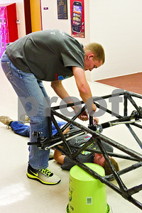 Photo by Shannon Wilson / Tyler Morning Telegraph Scott Lowrie (left) and Mack Stewart work together to install the rack and pinion steering parts in the solar car that they are building.