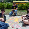 Jess Roberts, Zack Dobron and Nicholas Polichetti create a design during Sidewalk Chalk Day. Debby High — For Montgomery Media