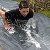 Fifth-grader Luke Austermehle slides fast down a soapy slip and slid to help clean the mud off. Debby High — For Montgomery Media