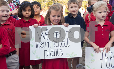 All Saints Episcopal School first graders Kate Patterson, 7, and Lucy Cozad, 6, hold signs during a dedication ceremony for the school's new learning farm Tuesday Oct. 10, 2017 in Tyler, Texas. All Saints Episcopal School has the largest school learning farm in the state of Texas. It is located on their campus and allows students to learn about farming from planting and harvesting plants to caring for egg-laying hens.  (Sarah A. Miller/Tyler Morning Telegraph)