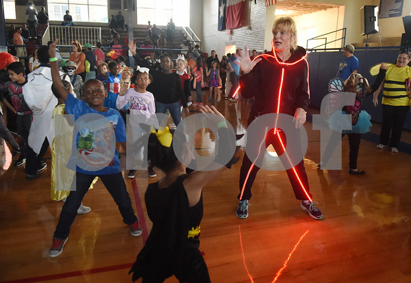 Physical education teacher Dyann Kemp, right, wears a light-up stick figure costume during the Sock Hop at Caldwell Elementary Arts Academy in Tyler Friday evening Oct. 21, 2016. The sock hop raised money to support the dance program which hosts a large dance showcase in the spring featuring every student in the school. Proceeds go toward costumes, building stage sets and other expenses.   (Sarah A. Miller/Tyler Morning Telegraph)