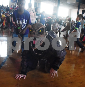 A student dressed as a dinosaur crawls on the floor at the Sock Hop at Caldwell Elementary Arts Academy in Tyler Friday evening Oct. 21, 2016. The sock hop raised money to support the dance program which hosts a large dance showcase in the spring featuring every student in the school. Proceeds go toward costumes, building stage sets and other expenses.   (Sarah A. Miller/Tyler Morning Telegraph)