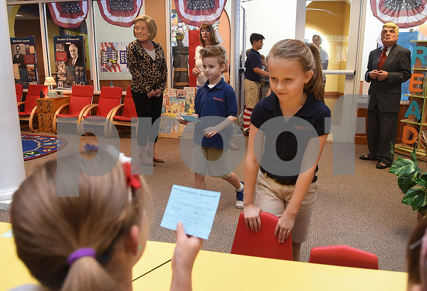Third grader Emma Harvey gives her voter registration card to a fifth grade volunteer during the mock election to help students learn about the process at The Brook Hill Lower School in Bullard Tuesday Nov. 1, 2016.  (Sarah A. Miller/Tyler Morning Telegraph)