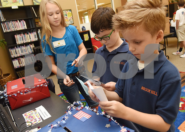 Fifth grader Brooklyn Davis mans the voting box as third graders Cooper Vilade and Gannon Welling turn in their ballots during the mock election to help students learn about the process at The Brook Hill Lower School in Bullard Tuesday Nov. 1, 2016.  (Sarah A. Miller/Tyler Morning Telegraph)
