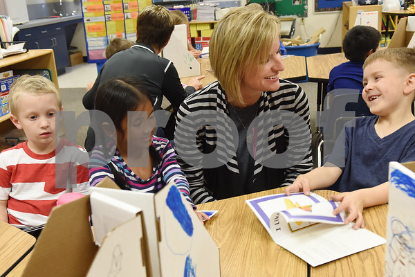 Early Childhood Center kindergarten teacher Angela Shine visits with students Isaac Willcox, 5, Melanie Phon, 6, and Joel Stanlety, 5, as they read their new books that they get to take home and keep Friday Nov. 18, 2016 as part of the Lindale Books for Kids program. Through this program every kindergarten, first and second grade student will receive 12 books each year.   (Sarah A. Miller/Tyler Morning Telegraph)