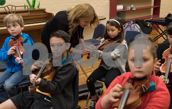 """Michelle Frederick helps student Kianna Sanchez, 9, play through """"Jingle Bells"""" during the beginners strings class Wednesday Nov. 1, 2017 at Caldwell Elementary Arts Academy. The class meets before school.  (Sarah A. Miller/Tyler Morning Telegraph)"""
