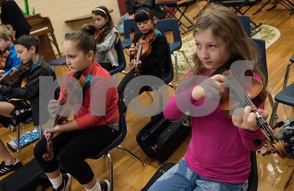 Student Annan Dubre, 9, practices plucking a song on the violin during the beginners strings class Wednesday Nov. 1, 2017 at Caldwell Elementary Arts Academy. The class meets before school.  (Sarah A. Miller/Tyler Morning Telegraph)