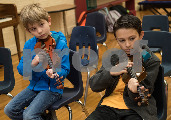 Students Joshua Davidson, 7, and Huntley Keel, 10, practice plucking a song during the beginners strings class Wednesday Nov. 1, 2017 at Caldwell Elementary Arts Academy. The class meets before school.  (Sarah A. Miller/Tyler Morning Telegraph)