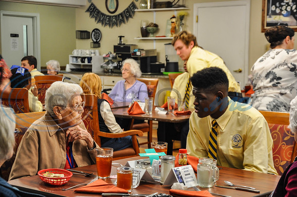 """Jeremy Singleton, 17, (right) a Jacksonville High School junior visits with Angelina House resident Louise Currier, 89, (left) during a """"Listen & Learn"""" event put on by the Jacksonville ISD Student Ambassador Team. The lunch was a part of the team's monthly community outings and was held on Thursday, November 8. (Jessica T. Payne/Tyler Morning Telegraph)"""