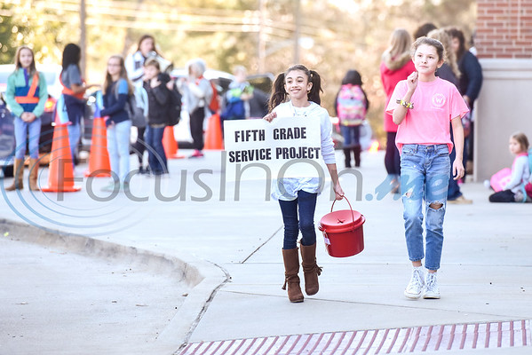 Bailey Parsons and Lilly Bouldin, both 10, collect donations after school as parents come to pick up their children for a fifth grade fundraiser in partnership with the Salvation Arm at Andy Woods Elementary in Tyler, Texas, on Monday, Dec. 10, 2018. (Chelsea Purgahn/Tyler Morning Telegraph)