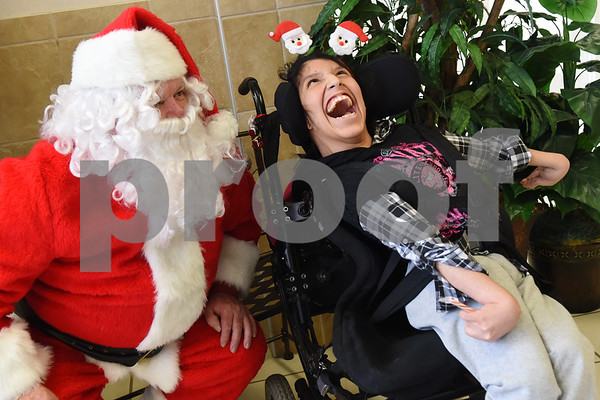 Santa Claus visits Julissa Almazan Wayne D. Boshears Center for Exceptional Programs Friday Dec. 9, 2016. Employees from Trane in the IUECWA Local 282 also visited students handing out gift bags filled with Christmas presents for each student. Boshears serves students with  severe and profound disabilities.  (Sarah A. Miller/Tyler Morning Telegraph)