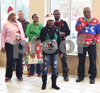 Trane employees including LaVera Robinson, center, hand out presents at Wayne D. Boshears Center for Exceptional Programs Friday Dec. 9, 2016. Employees from Trane in the IUECWA Local 282 visited students handing out gift bags filled with Christmas presents for each student. Boshears serves students with  severe and profound disabilities.  (Sarah A. Miller/Tyler Morning Telegraph)