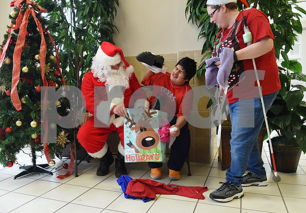 Danice Lambert helps student Arath Martinez with his new shoes and shirts he received from Santa Claus at Wayne D. Boshears Center for Exceptional Programs Friday Dec. 9, 2016. Employees from Trane in the IUECWA Local 282 also visited students handing out gift bags filled with Christmas presents for each student. Boshears serves students with  severe and profound disabilities.  (Sarah A. Miller/Tyler Morning Telegraph)
