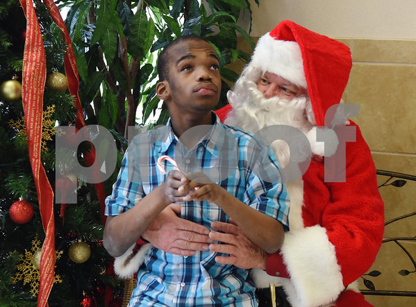 Santa Claus meets Alex Allen at Wayne D. Boshears Center for Exceptional Programs Friday Dec. 9, 2016. Employees from Trane in the IUECWA Local 282 also visited students handing out gift bags filled with Christmas presents for each student. Boshears serves students with  severe and profound disabilities.  (Sarah A. Miller/Tyler Morning Telegraph)