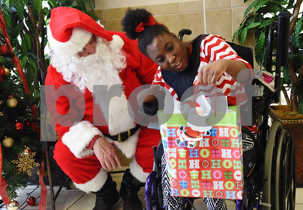 Alex Ginderatt receives a present from Trane employees and a visit from Santa Claus at Wayne D. Boshears Center for Exceptional Programs Friday Dec. 9, 2016. Employees from Trane in the IUECWA Local 282 visited students handing out gift bags filled with Christmas presents for each student. Boshears serves students with  severe and profound disabilities.  (Sarah A. Miller/Tyler Morning Telegraph)