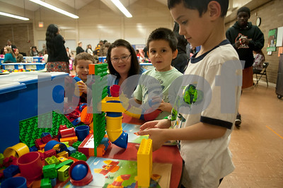 "Laurie Escuadra and her sons Favianno, 3, left, Filiberto, 4, center, and Fererico, 6, right, play with Legos during the Tyler ISD Head Start program ""Family Lego Night"" Thursday at the St. Louis Early Childhood Center.   (Sarah A. Miller/Tyler Morning Telegraph)"