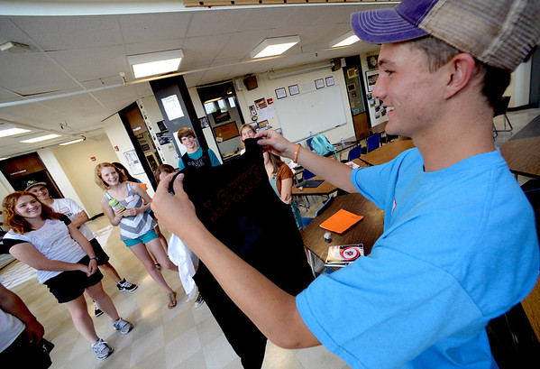 "Fairview upperclassman, Jackson Wojciechowski, right, hands out Olympic-themed T-shirts to his group of incoming freshman at Fairview High School on Wednesday.<br /> For a video and more photos of Fairview, go to  <a href=""http://www.dailycamera.com"">http://www.dailycamera.com</a>.<br /> Cliff Grassmick  / August 15, 2012"