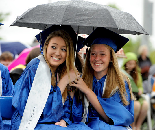 """Elizabeth McJannet-Bratton, left, and Lea Maxwell, share an umbrella during the Peak to Peak graduation on Saturday.<br /> For more photos and a video of Peak to Peak graduation, go to  <a href=""""http://www.dailycamera.com"""">http://www.dailycamera.com</a>.<br /> Cliff Grassmick / May 19, 2012"""