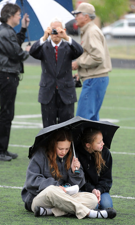 "Claire Hankla, left, and Jessica Shule, find shelter from the rain at the graduation ceremony.<br /> For more photos and a video of Peak to Peak graduation, go to  <a href=""http://www.dailycamera.com"">http://www.dailycamera.com</a>.<br /> Cliff Grassmick / May 19, 2012"