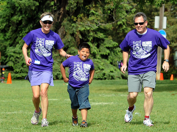 "Diana Kallgren, left, and Cliff Bosley, help Manual Garcia, 6, finish the race on Friday.<br />  About 450 students  participated in 35th Annual Columbine Elementary School Mile Marathon on Friday. For more photos and a video of the run, go to  <a href=""http://www.dailycamera.com"">http://www.dailycamera.com</a>.<br /> Cliff Grassmick / May 18, 2012"