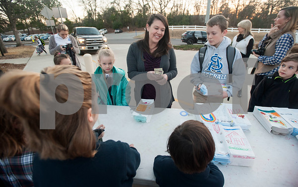 Kristen Courtney, center, buys a carton of eggs before school from All Saints Episcopal School first graders that they collected from their learning farm on Thursday Feb. 1, 2018. The students named their business Egg World.  (Sarah A. Miller/Tyler Morning Telegraph)
