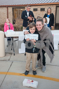 Nash Jones, 7, poses with his mom Amanda Jones and a carton of eggs before school on Thursday Feb. 1, 2018. First graders from All Saints Episcopal School collected eggs from their learning farm to sell. The students named their business Egg World.  (Sarah A. Miller/Tyler Morning Telegraph)