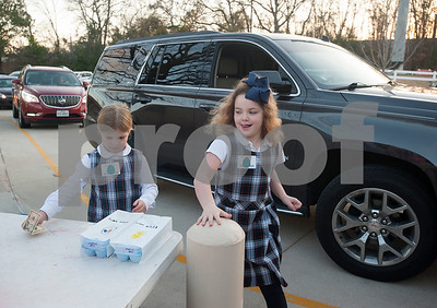 Katie Giordano, 7, and Sydney Macha, 6, take an order for eggs from a car in the drop-off lane at All Saints Episcopal School in Tyler on Thursday Feb. 1, 2018. First graders from All Saints Episcopal School collected eggs from their learning farm to sell. The students named their business Egg World.  (Sarah A. Miller/Tyler Morning Telegraph)