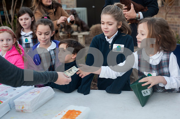Olivia Riepe, 7, collects money from a customer as she and her first grade class sells cartons of eggs before school on Thursday Feb. 1, 2018. First graders from All Saints Episcopal School collected eggs from their learning farm to sell. The students named their business Egg World.  (Sarah A. Miller/Tyler Morning Telegraph)