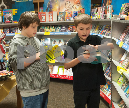 """Fifth grade students Orion Baker, 11, and Brayden Goodson, 11, look through books at the book fair during Math and Reading Night at Clarkston Elementary School Thursday Feb. 18, 2016. The event was Star Wars themed and featured math and reading game stations for students grades pre-kindergarten through fifth grade. """"The event helps the parents learn strategies to help their kids at home with math and reading,"""" event organizer Shannon Johnson said.   (Sarah A. Miller/Tyler Morning Telegraph)"""