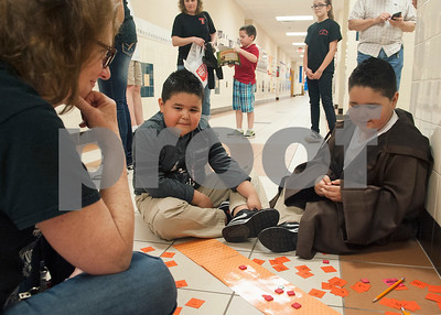 """Teacher Mary Ann Post assists second grade twins Max Morales, 7, and Ian Morales, 7, with a math game during Math and Reading Night at Clarkston Elementary School Thursday Feb. 18, 2016. The event was Star Wars themed and featured math and reading game stations for students grades pre-kindergarten through fifth grade. """"The event helps the parents learn strategies to help their kids at home with math and reading,"""" event organizer Shannon Johnson said.   (Sarah A. Miller/Tyler Morning Telegraph)"""