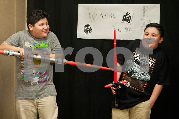 """Brothers Antonio Llano, 9, and Jesus Llano Jr., 11, fight with lightsabers inside a Star Wars photobooth during Math and Reading Night at Clarkston Elementary School Thursday Feb. 18, 2016. The event was Star Wars themed and featured math and reading game stations for students grades pre-kindergarten through fifth grade. """"The event helps the parents learn strategies to help their kids at home with math and reading,"""" event organizer Shannon Johnson said.   (Sarah A. Miller/Tyler Morning Telegraph)"""