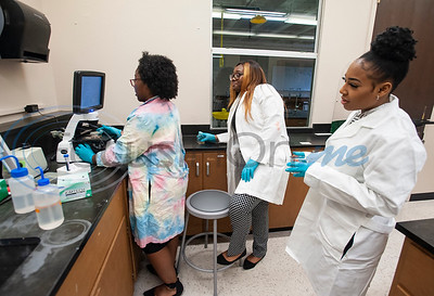 Jarvis Christian College students Kaejaren Caldwell, Dequaysha Greene and Chartaveoua Graggs work with treated cancer cells under a microscope in the biology lab Monday Feb. 18. Seven students will travel this week to Washington, D.C. to present their research on finding a cure for cancer at the Emerging Researchers National Conference.  (Sarah A. Miller/Tyler Morning Telegraph)