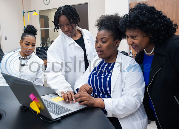 Kaayla Tippins, second from right, shows Dr. Glendora Carter her research poster on her computer during class on Monday Feb. 18, 2019. Seven Jarvis Christian College students will travel this week to Washington, D.C. to present their research on finding a cure for cancer at the Emerging Researchers National Conference.  (Sarah A. Miller/Tyler Morning Telegraph)