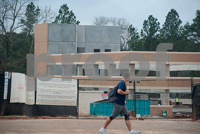 A student walks past a parking garage that is being built adjacent to the newly named Soules College of Business. on the campus of the University of Texas at Tyler on Monday Feb. 19, 2018.   (Sarah A. Miller/Tyler Morning Telegraph)