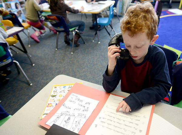 """Phineaus Cohen uses a whisper phone to proof read his story at Emerald Elementary in Broomfield, Colorado February 22, 2013.  DAILY CAMERA/ MARK LEFFINGWELL<br /> <br /> See video of kids from Emerald Elementary and Sanchez Elementary working on their stories at  <a href=""""http://www.dailycamera.com"""">http://www.dailycamera.com</a>"""