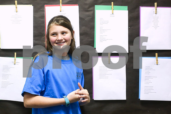Anna Hall smiles as she stands next to a poem she wrote at the Bridgemark Center in Tyler, Texas, on Monday, Feb. 27, 2017. Bridgemark Center specializes in education for children with learning disabilities such as dyslexia, dysgraphia and dyscalculia. (Chelsea Purgahn/Tyler Morning Telegraph)