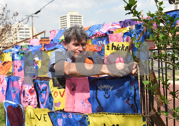 Derek Frazier of Tyler Museum of Art  helps tie student decorated flags to a collaborate art piece by University of Texas at Tyler graduate art student Joanna Gifford Caldwell Elementary Arts Academy students.    (Sarah A. Miller/Tyler Morning Telegraph)