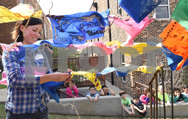University of Texas at Tyler graduate art student Joanna Gifford ties flags decorated by Caldwell Elementary Arts Academy students to her art instillation Friday at the school called Bridge: Compassion.   (Sarah A. Miller/Tyler Morning Telegraph)