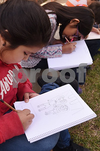 Fourth grader Marlenee Arriaga, 10, draws a design for a flag in her sketchbook Friday March 3, 2017 at Caldwell Elementary Arts Academy. University of Texas at Tyler graduate art student Joanna Gifford is working with Caldwell students on a collaborative art instillation at the school. Flags created by students on the structure will represent the theme of compassion.  (Sarah A. Miller/Tyler Morning Telegraph)