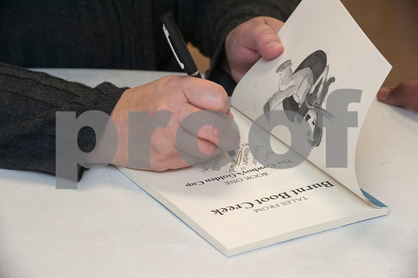 """Author Bridgette Booth autographs a copy of her children's chapter book """"Tales from Burnt Boot Creek: The Cowboy's Golden Cup"""" during a special event at Promise Academy in Tyler on Friday March 9, 2018.   (Sarah A. Miller/Tyler Morning Telegraph)"""