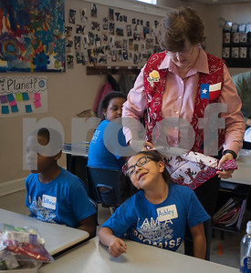 Promise Academy second grader Ashley Flores, 8, tilts her head as a volunteer ties a bandana around her neck during an interactive event put together by the Ladies Book Study from Redeemer Presbyterian Church in Tyler at their school in Tyler on Friday March 9, 2018.   (Sarah A. Miller/Tyler Morning Telegraph)