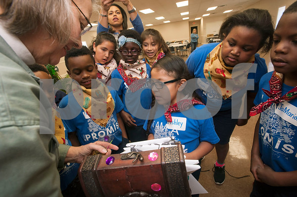 Patti Babin, a member of the Ladies Book Study from Redeemer Presbyterian Church in Tyler, left, opens a chest to reveal the prize at the conclusion of a treasure hunt at Promise Academy in Tyler on Friday March 9, 2018.   (Sarah A. Miller/Tyler Morning Telegraph)
