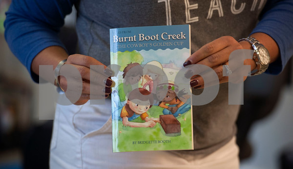 """Promise Academy teacher Gloria Johnson holds a copy of author Bridgette Booth's children's chapter book """"Tales from Burnt Boot Creek: The Cowboy's Golden Cup"""" during a special event at Promise Academy in Tyler on Friday March 9, 2018.   (Sarah A. Miller/Tyler Morning Telegraph)"""