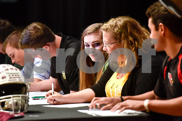 Molly Harris, center, watches as Audrey West signs her letter during signing day at Whitehouse High School in Whitehouse, Texas, on Tuesday, March 21, 2017. (Chelsea Purgahn/Tyler Morning Telegraph)