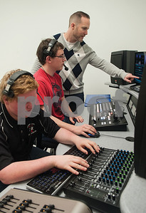 Teacher Jason Bethany works with Robert E. Lee High School junior Michael Chandler in the director's booth during an audio/video production class at the Tyler ISD Career and Technology Center Tuesday Feb. 23, 2016. Also pictured is REL junior Colin Weaver operating the sound board.  (Sarah A. Miller/Tyler Morning Telegraph)
