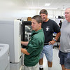 New engineering instructor Malcolm Paradise and  engineering instructor Dennis Cormier watch as senior Jamison LaRoche, 17, who has been helping the teachers out this summer, works with the 3D printer in the engineering program at Montachusett Regional Vocational Technical School on Wednesday afternoon. SENTINEL & ENTERPRISE/JOHN LOVE