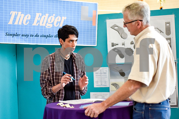 Robert E. Lee student Uriel Morales, 17, speaks to Greig Latham about his product at the Tyler ISD Career And Technology Center in Tyler, Texas, on Thursday, April 13, 2017. The center hosted its first Trades Show, which showcased senior projects from engineering, design and development, auto collision repair, architectural design, construction, marketing and more. (Chelsea Purgahn/Tyler Morning Telegraph)