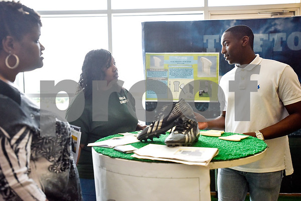 Felecia Jones and Roslyn Jones listen to Robert E. Lee student Royland Black, 18, talk about his product at the Tyler ISD Career And Technology Center in Tyler, Texas, on Thursday, April 13, 2017. The center hosted its first Trades Show, which showcased senior projects from engineering, design and development, auto collision repair, architectural design, construction, marketing and more. (Chelsea Purgahn/Tyler Morning Telegraph)