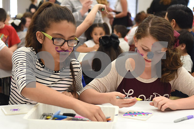 Fifth graders Nayli Carrillo, 11, and Lorelai Walker, 11, wear facepaint as they draw on tiles during the annual Art Gallery Walk at Bell Elementary School in Tyler Thursday. It was the 10th year for the event which features a piece of artwork from every student in the school.  (Sarah A. Miller/Tyler Morning Telegraph)